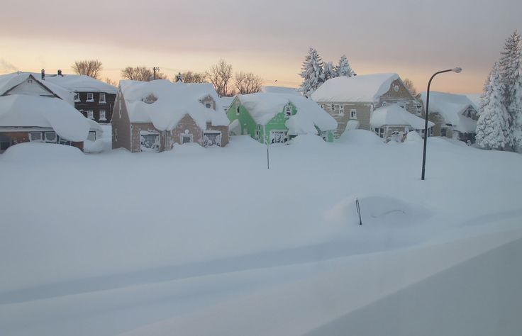 Snow covers a street at daybreak Wednesday, Nov. 19, 2014, in south Buffalo, N.Y. ..LG....d and snow roll across the country