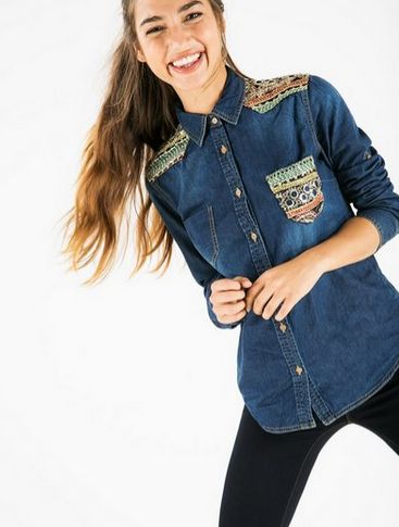Denim shirt with sparkly, metal, multicolored details along the pocket and shoulders.