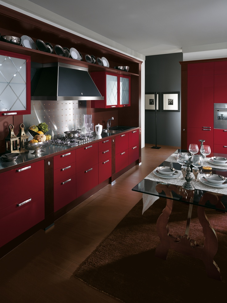 Baccarat by Gianni Pareschi. #kitchens #red #Scavolini #classickitchens The keynotes of Baccarat with Wax Red gloss lacquered doors are its shine, its luxury and its dreamy aura. However, the modern features that bring the kitchen firmly up to date are also very attractive. These include the wall cladding, the hood, the steel and the cupboards.