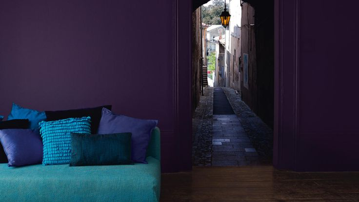 Sala de estar decorada com tons de roxo exuberantes, azul esverdeado e turquesa