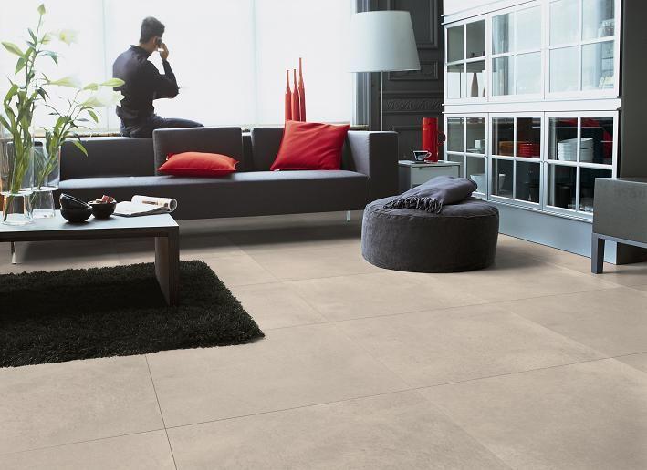 Vloertegels van beton in grote vierkanten tegels, in een lichtgrijze kleur. Voordeel: Het is makkelijk schoon te maken en het heeft een lichte kleur, waardoor het een lichte uitstraling krijgt. Nadeel: Er komen makkelijk krassen op en doordat het een lichte kleur heeft, moet je het vaker schoonmaken.