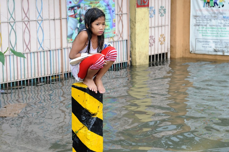 Monsoon Rain Floods Manila - A soaking wet child sits on a post on a flooded street in suburban Manila, on August 8, 2012. More than one million people in and around the Philippine capital battled deadly floods on August 8 amid relentless monsoon rains, not predicted to let up until Thursday at the earliest. (Jay Directo/AFP/Getty Images) # - In Focus - The Atlantic
