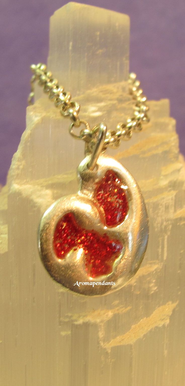 Cute little pure silver Aromapendant with sparkly red resin spots. It is 2cm long and priced at only $40.00. With a drop of essential oil placed in the back, this warms gently against the body and becomes a wearable, personal aromatherapy diffuser. Made by Julie Primmer.