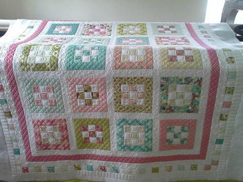 "Free quilt pattern from Moda Bake Shop - 2"" nine-patch blocks and 2"" sashing, 1"" colored border, 2"" white and colored squares border between 2 white 2"" borders. approximately 66.5″ x 90.5″"