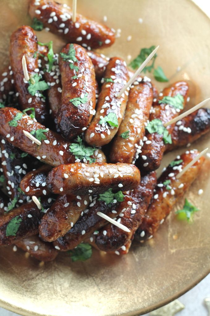 STICKY ASIAN COCKTAIL SAUSAGES -- The ultimate Christmas party food! Cocktail sausages baked to perfection with a sweet and sticky Asian glaze