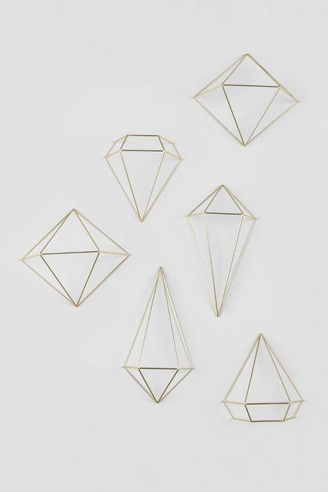 "The Gold Prism Wall Decor features a set of 6 three-dimensional geometric shapes that can be mounted onto any wall or hung from the ceiling to create a unique look!<br /> <br /> Set of 6:<br /> - 2 prisms measuring 12"" x 6.5"" x 3""<br /> - 2 prisms measuring 9.5"" x 8.5"" x 5""<br /> - 2 prisms measuring 7.5"" x 7"" x 3.5""<br /> <br /> - Includes tools to mount on wall (wall mounts)"