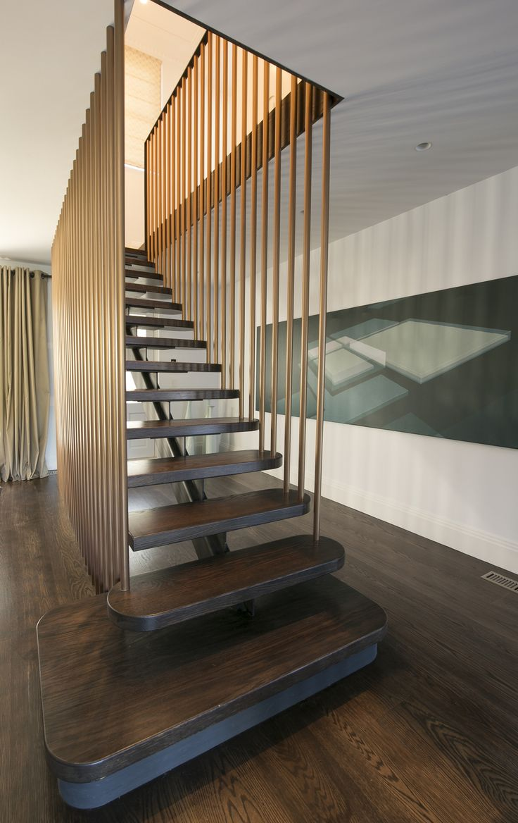 Floating stairwell in dark stained oak and gold painted steel
