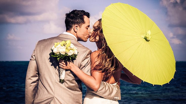 Picture perfect bride and groom kiss under a parasol | Palace Resorts Weddings ®