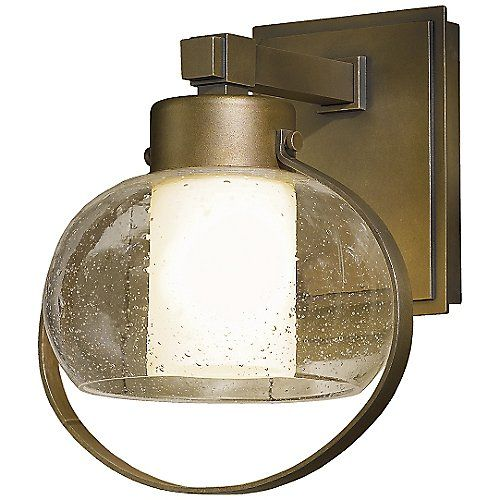 The Hubbardton Forge Port Coastal Outdoor Wall Sconce with Seeded Glass will provide a welcoming presence to the entrance of your home with its bulbous hand blown glass shade and shimmering finish. A large ring circles around the glass, adding visual tension and negative space into this simple piece. The coastal finishes are meant to endure harsh salt water environments and have been tested to 100% humidity and water with salinity 50% greater than the average found in the Atlantic or…