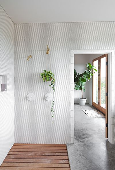 concrete floors, open shower with wood floor, walls of mini white hexagon tile, doorway framed in white subway tile