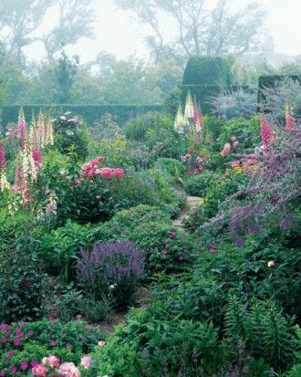 Nantucket, Massachusetts, a narrow path is flanked by exuberant mounds of colorful flowers, including foxgloves, cranesbills, and peonies.