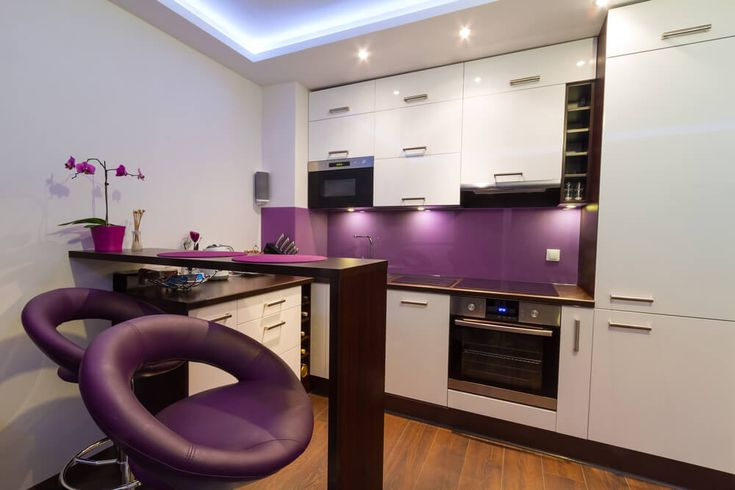 Small apartment kitchen with purple back splash and stools. Cabinets in white. Kitchen floor is wood.