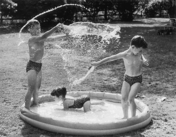 23 Vintage Photos That Show What Summer Fun Looked Like Before The Internet --- Three children in swimsuits splash around in a paddling pool, circa 1950. (Photo by FPG/Hulton Archive/Getty Images)