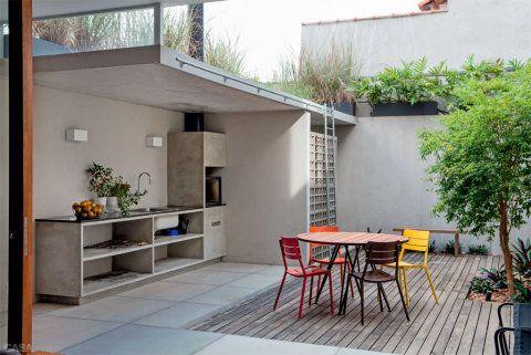 No terraço dos fundos, a parte coberta protege a churrasqueira e a área de serviço. Uma escada leva à horta do telhado. Mesa Nômade e cadeiras Bee (Fernando Jaeger).