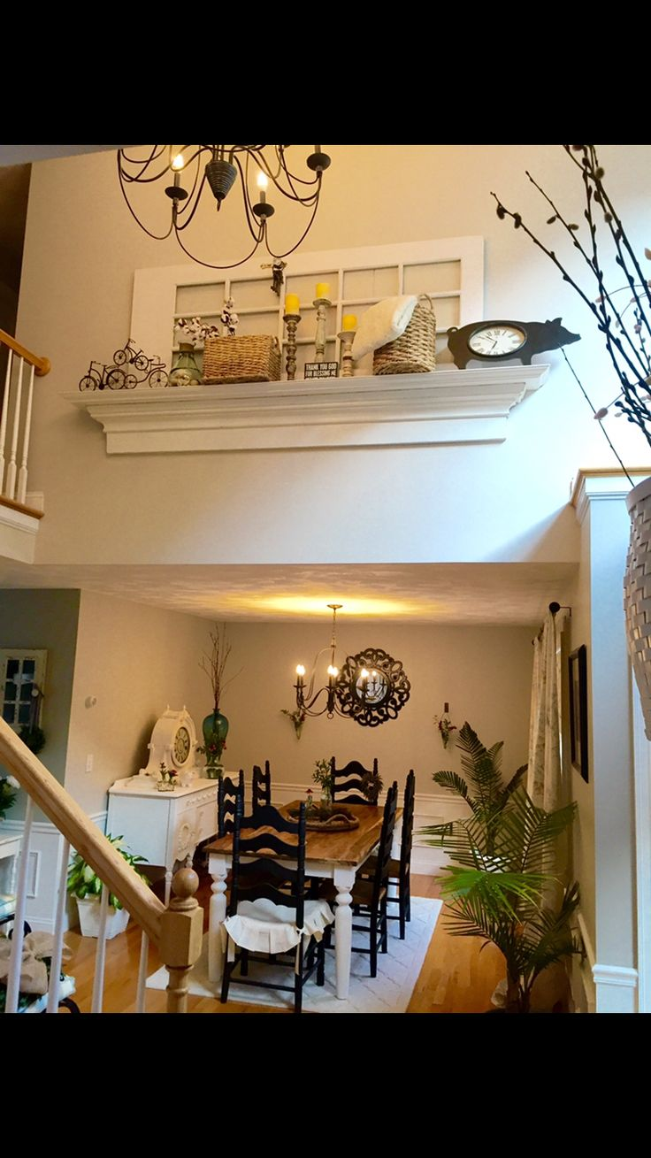 Repurposed door and mantle shelf placed on wall in two-story foyer above dining room. Loving the Farmhouse inspiration.