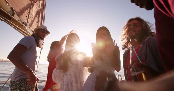 Group of friends enjoying a party on a yacht, laughing and dancing while holding…