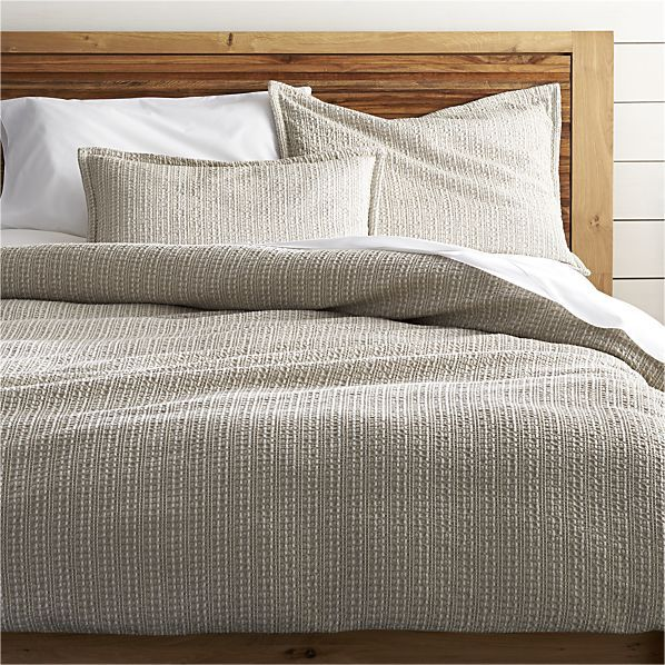 Tonal taupes highlight the beautiful texture of Tessa's dimensional Jacquard weave. Woven of spun cotton, the fabric is given an enzyme finish for ultimate softness. Smooth cotton backs the duvet, which closes with gorgeous wood buttons. Reversible shams have subtle flange detailing and hidden zipper closures. Duvet inserts and bed pillows also available.