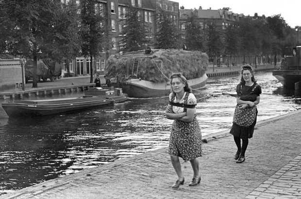 AMSTERDAM - Een zwaar beladen dekschuit met vers hooi, wordt door twee vrouwelijke familieleden van de schipper, voortgetrokken door de Kostverlorenvaart aan de Baarsjesweg in Amsterdam West. Jagen-vrouwen-boot 28 augustus 1943 Wo Oorlogsjaren. ANP PHOTO J D Noske