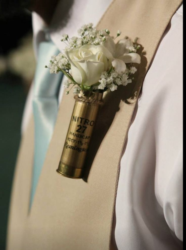 Hit the mark with this  shotgun shell boutonnière ! Shotgun shell is filled with million star baby's breath a white spray rose and a bloom of stephanotis- a look any outdoors man wouldn't mind wearing !