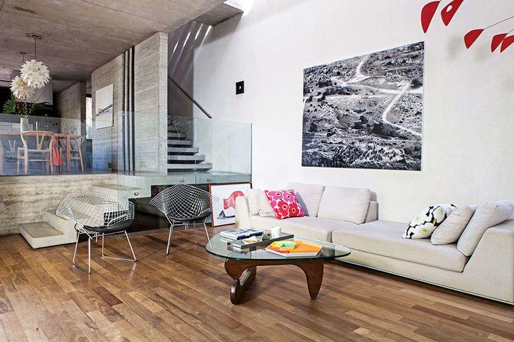 """Una versión moderna de la """"casa chorizo""""  La vista desde el living hacia el comedor y la escalera que lleva a los cuartos. En el piso, contra el cristal laminado que preserva la escalera y los vacíos, un cuadro del artista Máximo Pedraza. En la pared, 'Costanera', de Fabián Attila. Foto:Living/Javier Picerno"""