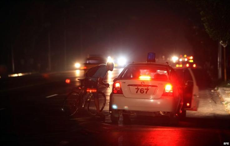 Un ciclista conversa el 9 de septiembre de 2012, con dos policías en una calle afectada por un apagón, en La Habana (Cuba).