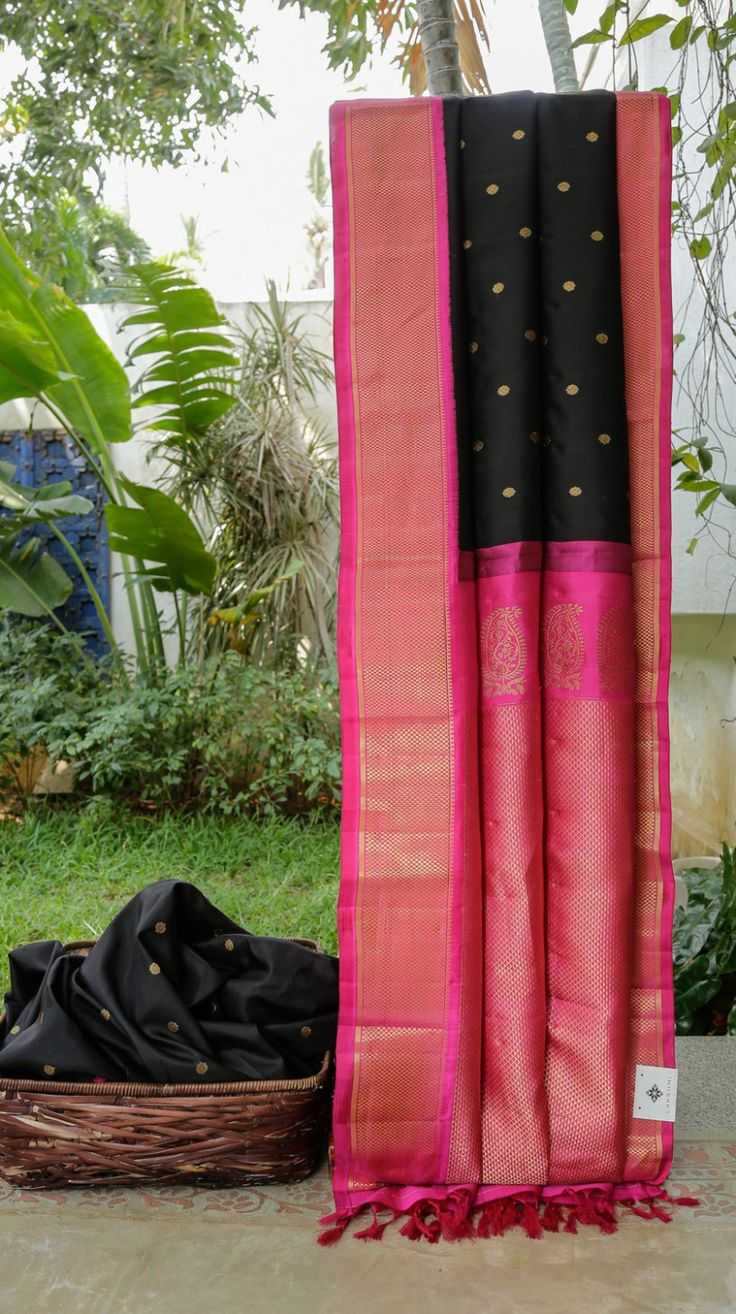 This black gadwal silk has small, gold zari bhuttas all over. the border and pallu are in magenta intricately woven with gold zari making it perfect for the upcoming wedding season