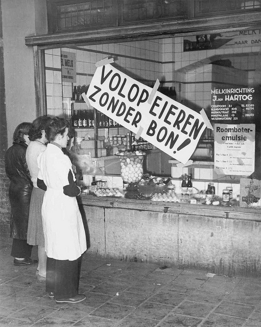 """December 1948. Women in front of dairy shop """"Melkinrichting J. den Hartog"""" in Amsterdam with inscription """"Plenty of eggs without distribution coupon!"""" Up to four years after the second world war had ended many products were still rationed. Photo collection AHF Amsterdam / Ben van Meerendonk"""