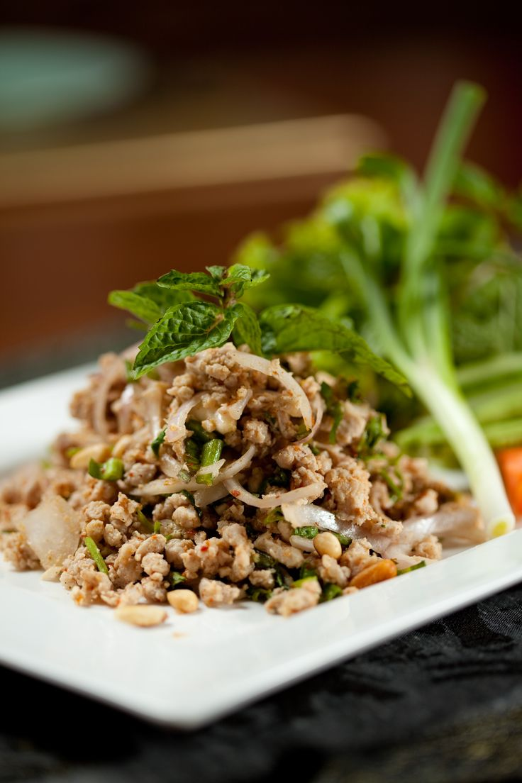LARB KAI - CHICKEN MARINATED WITH LIME JUICE AND HERBS SALAD. Our minced chicken is marinated in lime juice, then cooked in a blended fish sauce, spiced with chilli, spring onion, shallots, coriander leaf, saw leaves, roasted rice powder, mint leaves, and pine nuts; it is served on a bed of lettuce and fresh garden vegetables.