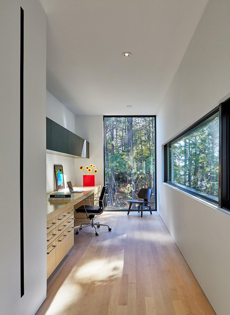 The home office has a floor-to-ceiling window with views of the surrounding nature.