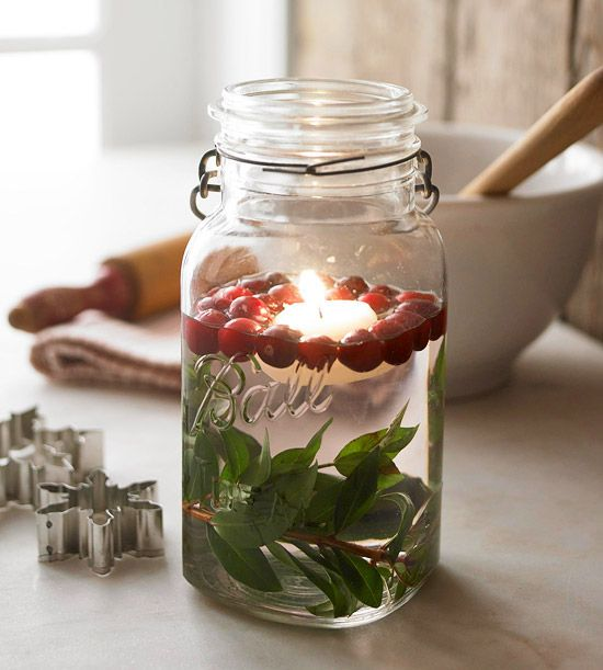 Love this look for a Christmas party! so soft, easy, & elegant! Natural Light:: Cast a warm glow on long winter evenings. Place a branch of greenery at the bottom of a glass jar or vase. Fill the jar about two-thirds full with water. Drop in cranberries and a floating candle. Its soft, flickering flame will add ambience to your dinner-party table.  Use soy or beeswax candle!