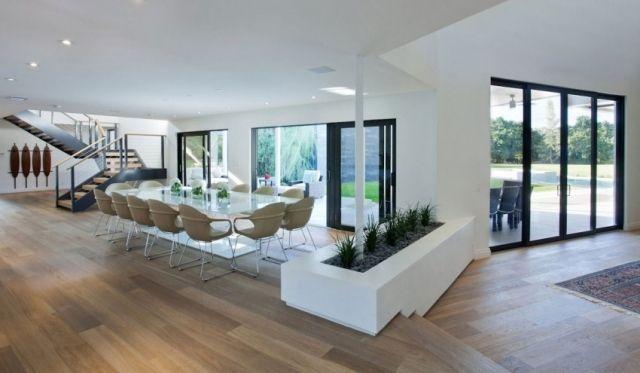 grande salle à manger avec sol en bois et baies vitrées