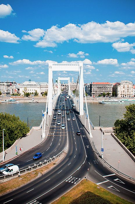 Erzsébet Hid - Elizabeth Bridge - Budapest. Spanning the Danube at its narrowest point through the city, it was built 1961-1964 and named for Elisabeth of Bavaria, a popular and loved Empress of Austria-Hungary assassinated in 1898. The bridge is on the foundations of the original bridge destroyed in WWII along with all the bridges in the city.