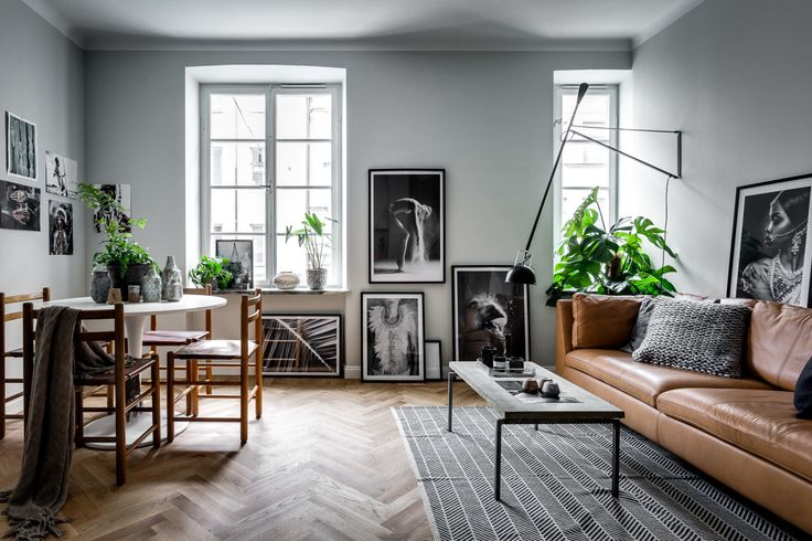 Grey art-filled living room with tan leather sofa