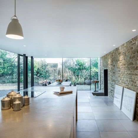 The sliding glass doors from IQ Glass offer minimal 21mm framing whilst the fixed glass inserts framelessly into the stone wall