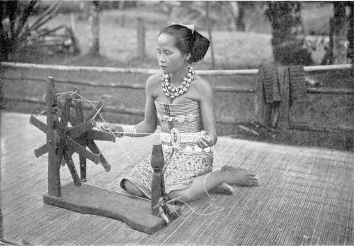 Dayak girl spinning, circa 1900