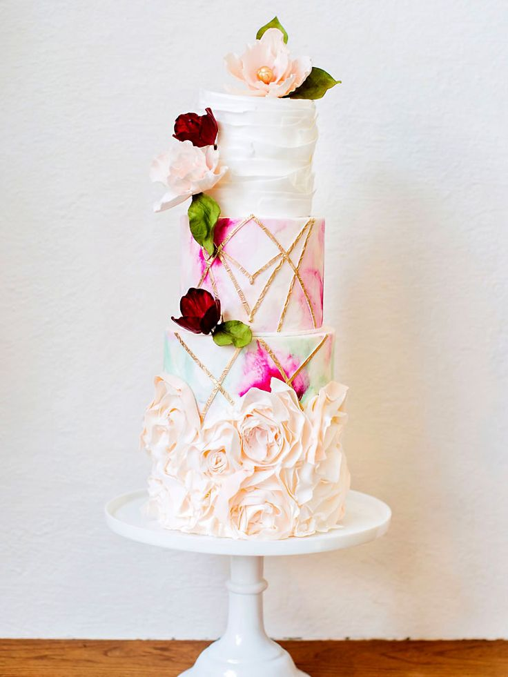 This four-tier wedding cake combines ruffles, watercolour, texture and blooms. The inspiration came from the striking allure of geometry-based graphic illustrations.