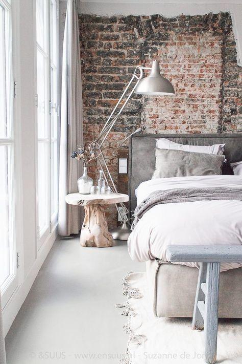 Un mur de briques et un chevet en bois dans la chambre