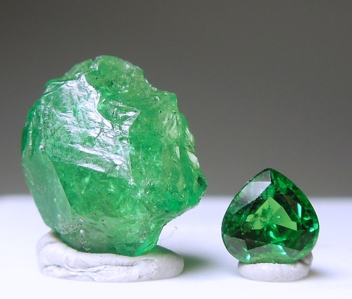 A beautiful set of rough and cut with a vivid green piece of rough with gemmy portions and a pear cut gem.