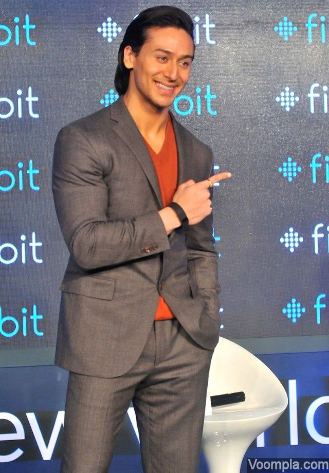 Tiger Shroff looking handsome in a grey suit paired with a rust coloured T-shirt and a slicked back hairstyle. via Voompla.com