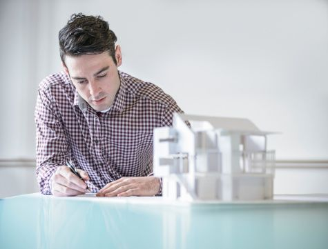 Architect working next to model building