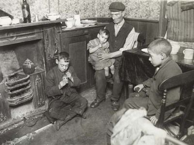 This photograph entitled 'Convicts home in Bethnal Green' taken 1900-1910 shows an elderly man looking after his Grandchildren whilst the mother goes out to work as a domestic cleaner. She is the sole breadwinner in the family as her husband is in prison.