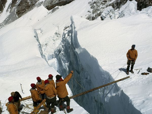 Crossing a Crevasse on Everest. Members of the 1963 American expedition wait for their turn to cross an Everest crevasse. One team member died trying to reach the summit, and the photographer of this picture lost toes and fingers to frostbite.