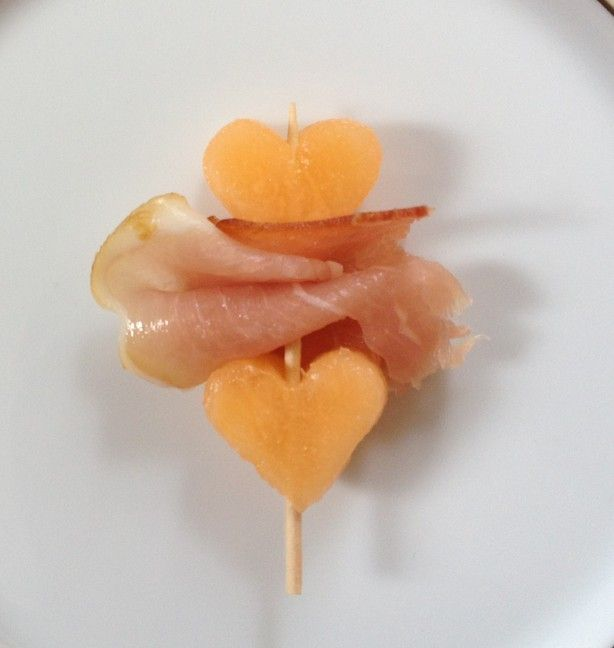 Maak met hart vormpje hartjes van meloen, en prik deze op een cocktail prikker met serano ham ertussen, dan is het niet zo'n grote hap, en ziet er leuk uit!