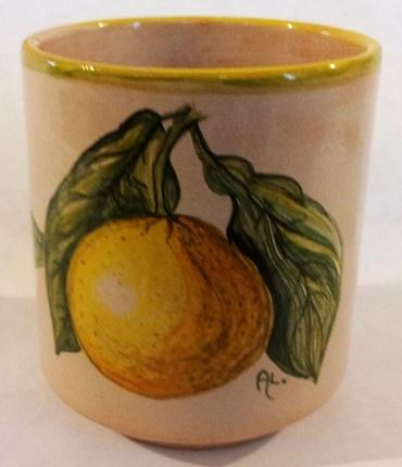 Bicchiere in ceramica con illustrazioni di fiori e frutta.