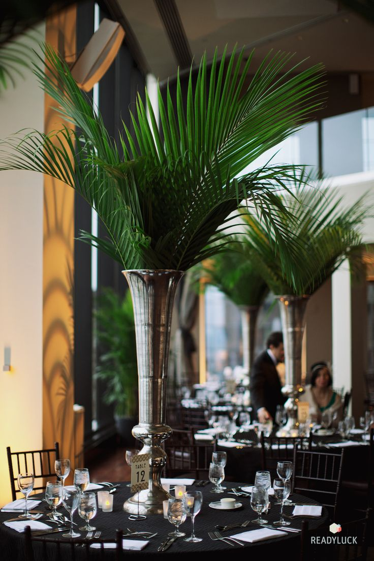 Tall, palm branch centerpiece. We like this as an option for a simple but high-impact tall arrangement. These would not be many and perhaps reserved for tables on the sides of the space to frame the center.