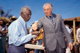 Prime Minister Gough Whitlam pouring soil into the hands of traditional owner Vincent Lingiari.