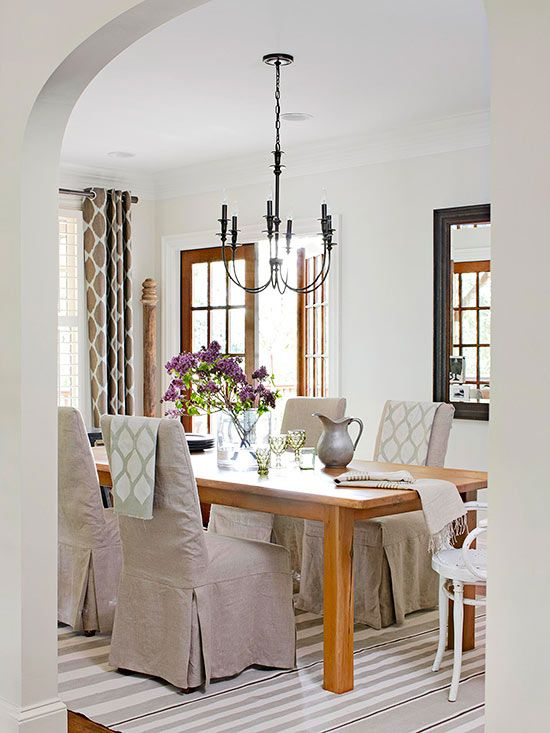 Beautiful neutral dining room with color added by draping small throws over the backs of chairs