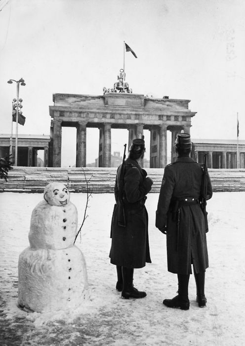Two West Berlin policemen with their new American rapid fire rifles on duty with a snowman on Christmas Day in front of the Berlin Wall at the Brandenburg Gate, 25th December 1961.