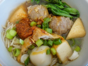 meat ball served with some vegetables, tofus and leeks,,
