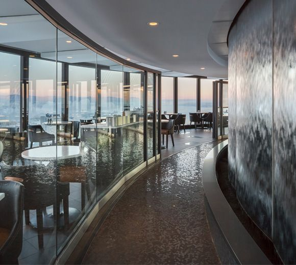 LEMAYMICHAUD | CIEL | Québec | Architecture | Design | Restaurant | Eatery | Hospitality | Bistro | Bar | Natural light | View | Sky | Seating | Chairs | Tables | Lighting | Graphic Deign | Architectural Glass | Fountain | Waterfall | Water Indoor
